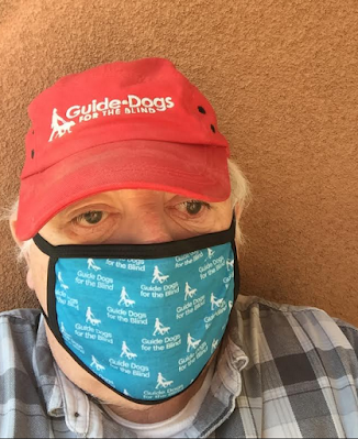 William wears a red Guide dogs for the blind baseball cap and a GDB facemask. He is looking dirctly into the camera