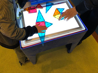 child and adult putting together Magna-Tile snowflakes on light panel