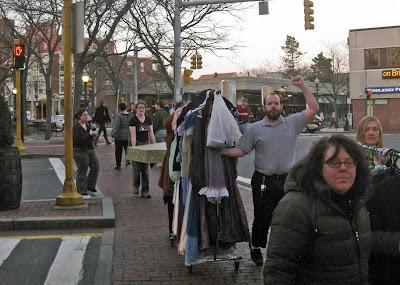 The cast and crew of Pride & Prejudice move set and costumes through Davis Square.