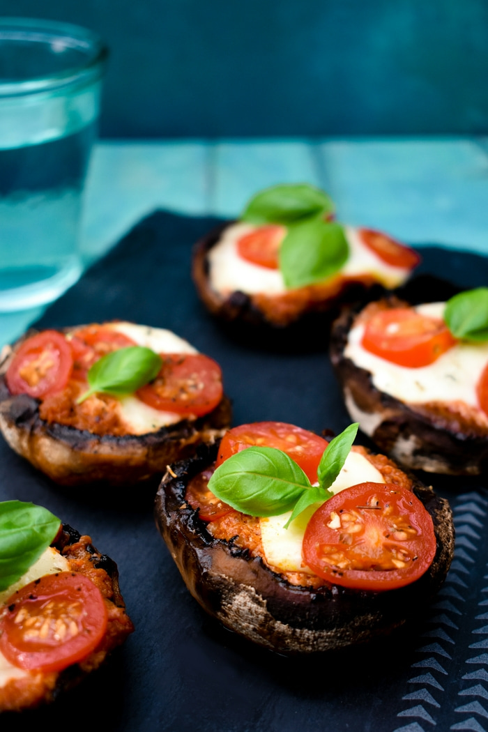 BBQ Pizza Stuffed Mushrooms, topped with fresh basil and served on a black slate board