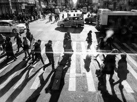 Black and white image of people walking across a pedestrian crossing