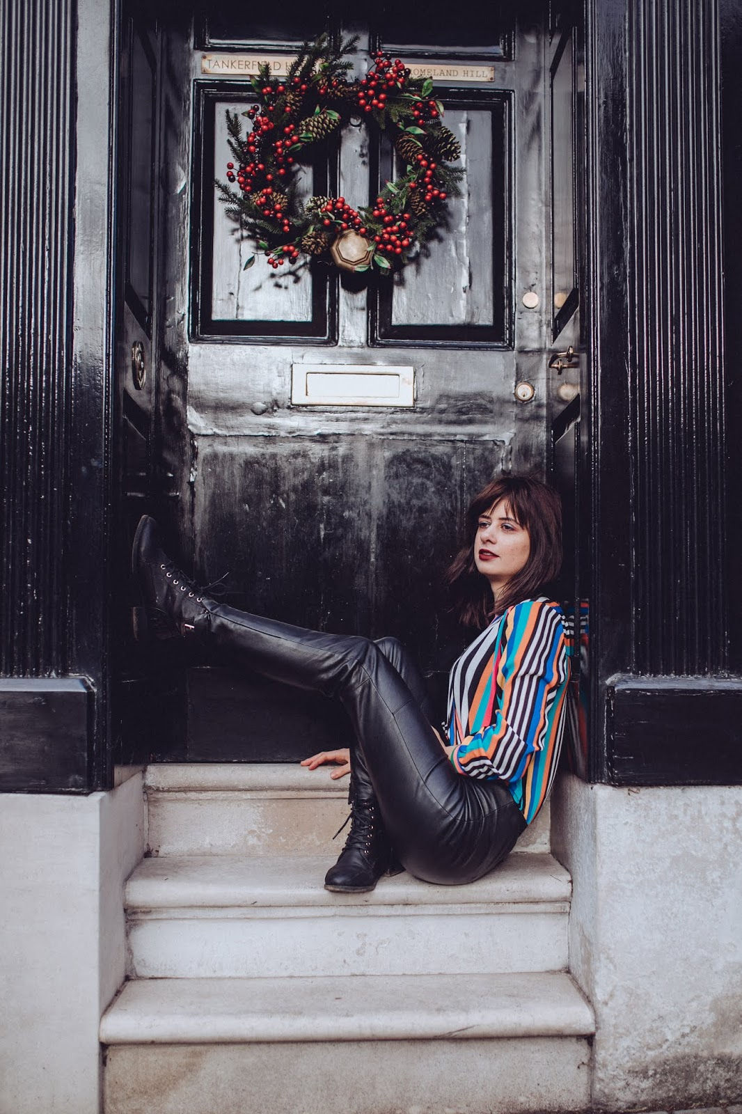 Laura is sitting on some steps. In front of a black door with a red christmas wreath