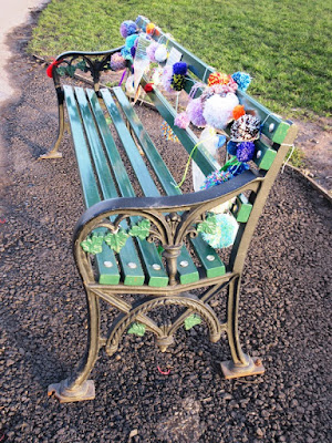 Park bench decorated with pom poms