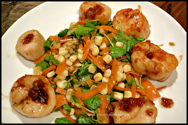 A colorful salad of corn, shredded carrots and greens surrounded by six caramelized scallops arranged on a white plate.