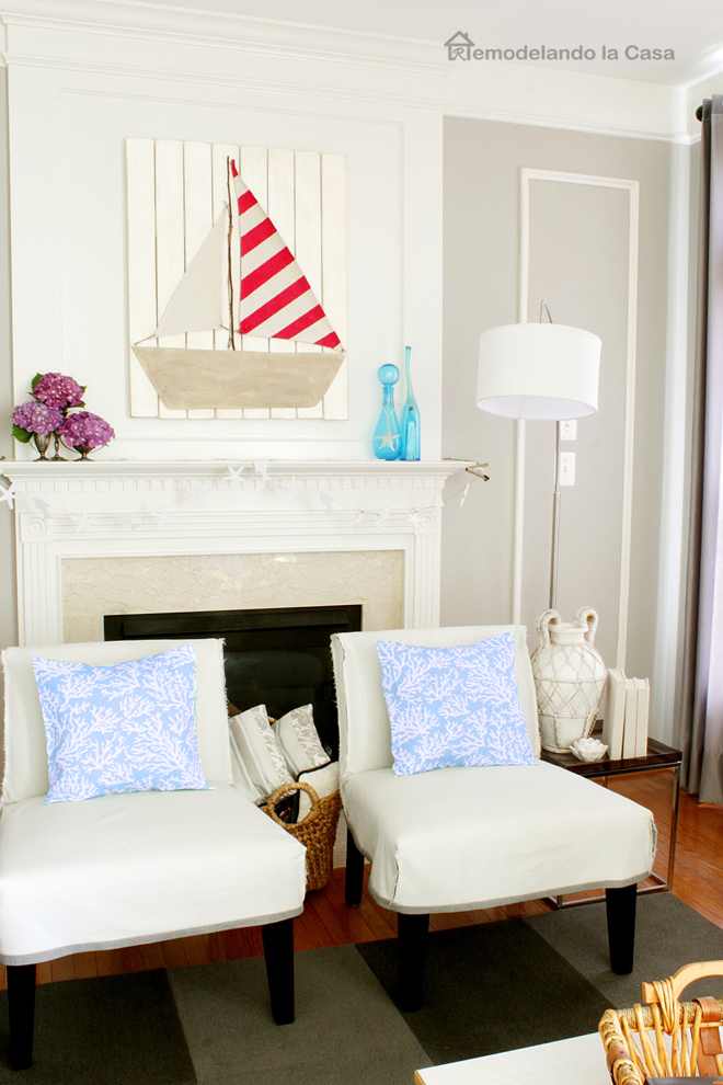 family room with fireplace and sailboat art - white chairs, lamp, basket