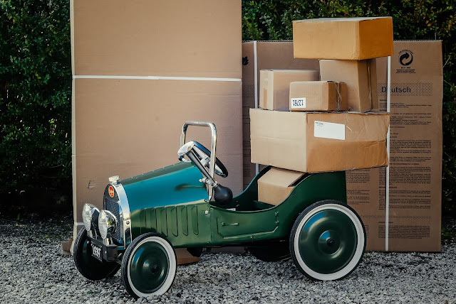 A green vintage car parked in front of big packages.