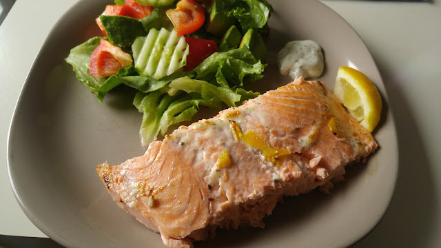 A plate of salmon with dill sauce and salad on the side.