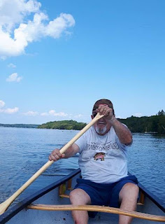 A senior paddling a canoe on Bass Lake.