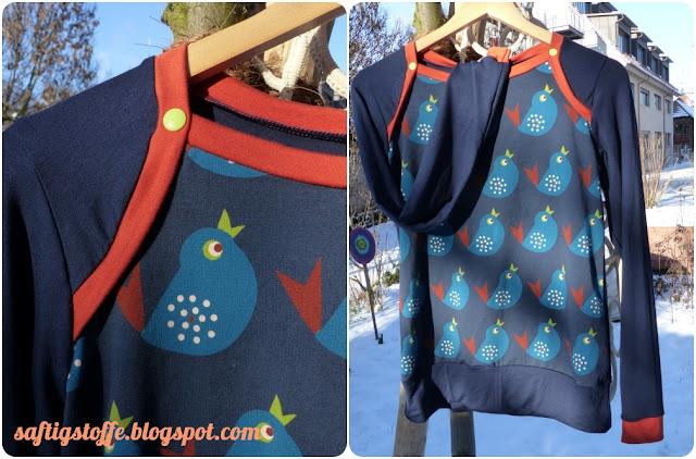 Sporty in Blau mit petrol-farbenem Vögelchen-Muster und orangen-farbenen Bündchen und Halsausschnitt.