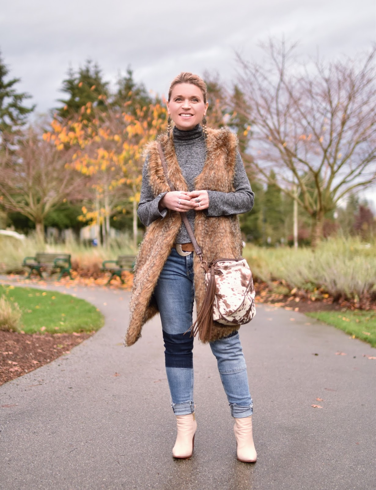 Monika Faulkner outfit inspiration - styling a faux-fur vest with a turtleneck sweater, patchwork skinny jeans, and Ivory booties