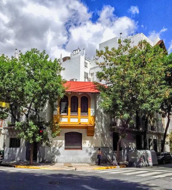 Casa en esquina con techo de tejas rojas,bordeada de árboles y con el cielo con nubes