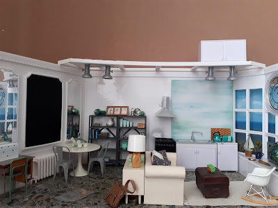 1/12 scale modern miniature scene of a kitchen, dining room and lounge in shades of white, teal, grey and light wood in a flat overlooking the sea.