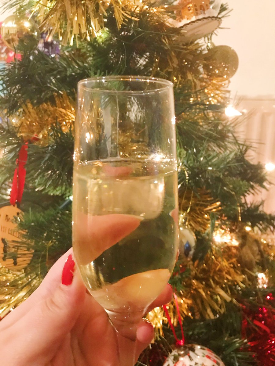 champagne glass held up in front of christmas tree