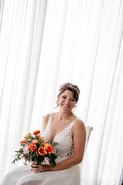 Bride with white background and bright floral bouquet.