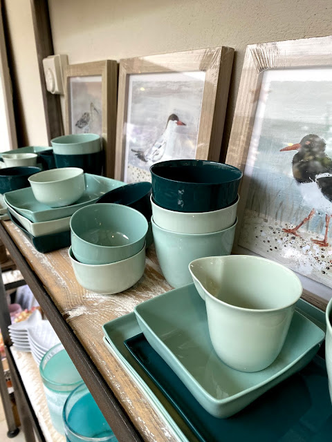 pretty ceramics in cream and greens, and bird paintings on shelves at a homeware shop in Burnham Market Norfolk