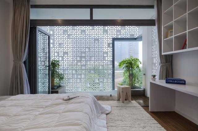 Phòng ngủ bày trí nhẹ nhàng với giường thấp sàn và ô cửa rộng thoáng.
