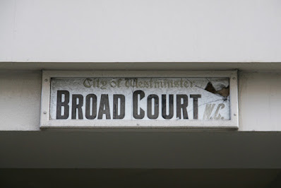 Photograph of a sign mounted on a concrete alleyway roof, white with faded lettering saying 'City of Westminster' in a gothic-type typeface, 'BROAD COURT' in thick, narrow typeface, and 'W.C.' in faded italic type.