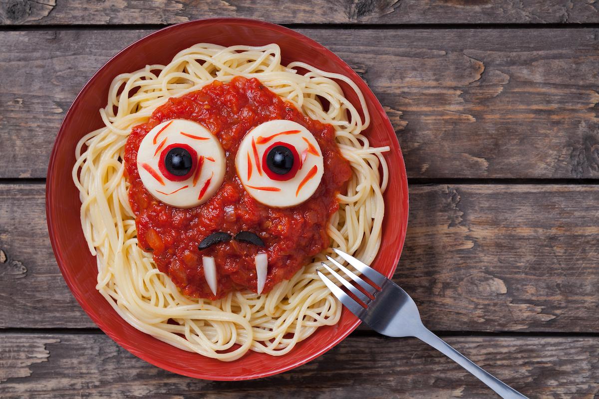 Plato de espaguetis con cara hecha con verduras y aceitunas