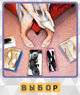девушка на диване выбирает себе туфли из коробок на полу