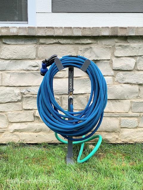 Move outdoor spigot with hose holder