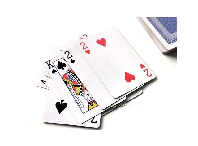 na zdjęciu stos kart odrzuconych a na wierzchu król pik, dwójka pik i dwójka kier