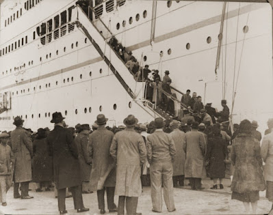A large crowd of people stand on the dock, watching passengers descend the stairs from an ocean liner. Black and white.