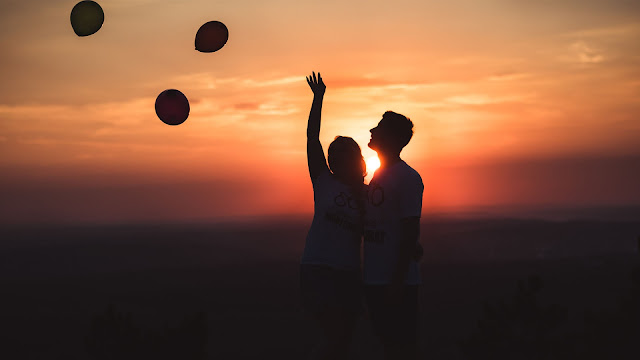 Couple happy together with baloons at sunset