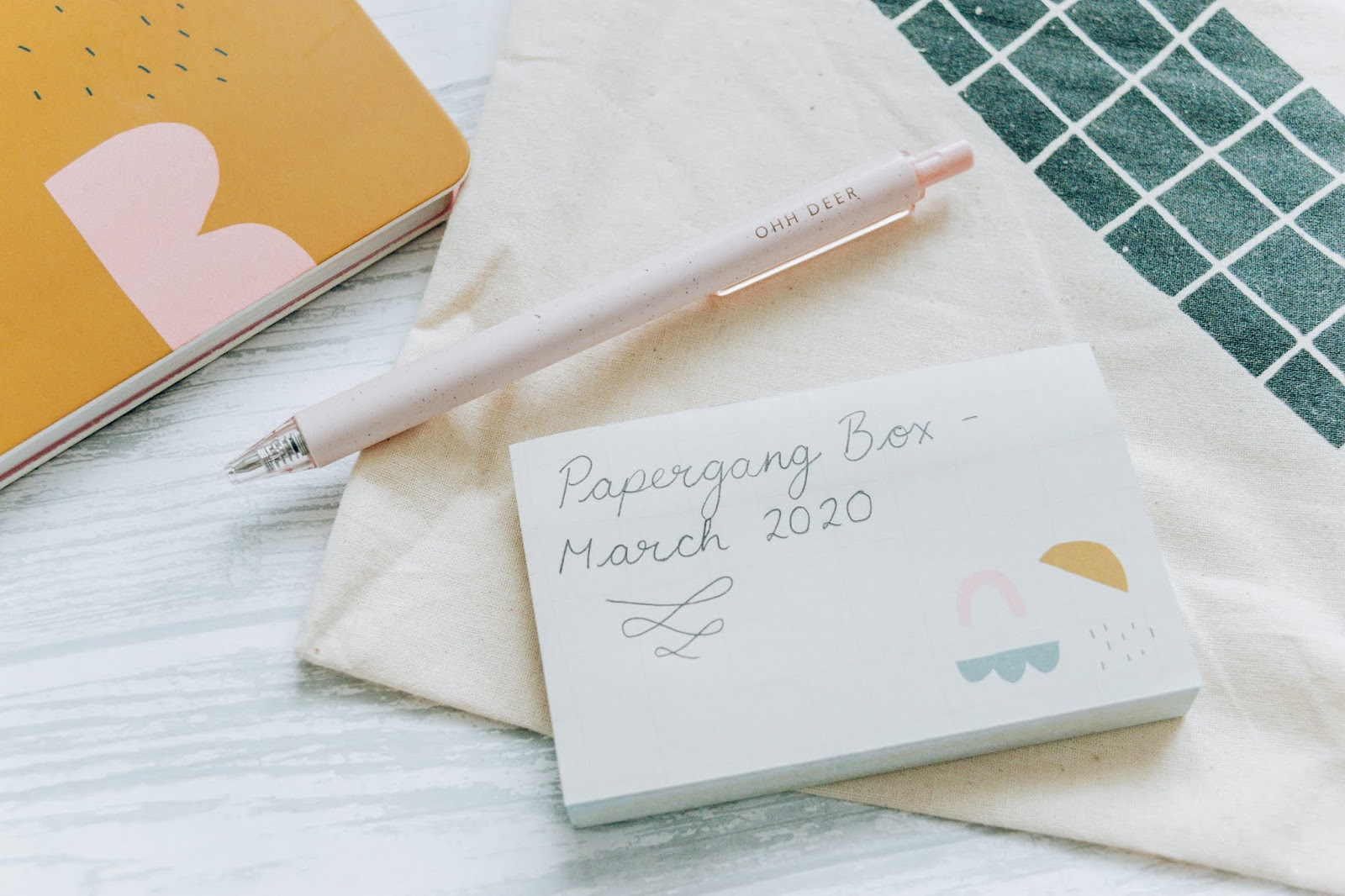 Beige sticky notes with geometric shapes and black writing on with a pink eggshell pen sitting on top.