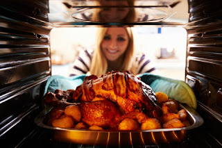 Photo of a woman checking on a turkey in the oven