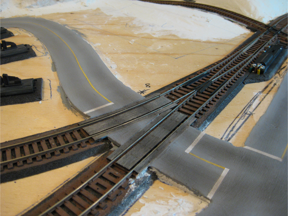 Completed model railroad plaster roads at a turnout and grade crossing