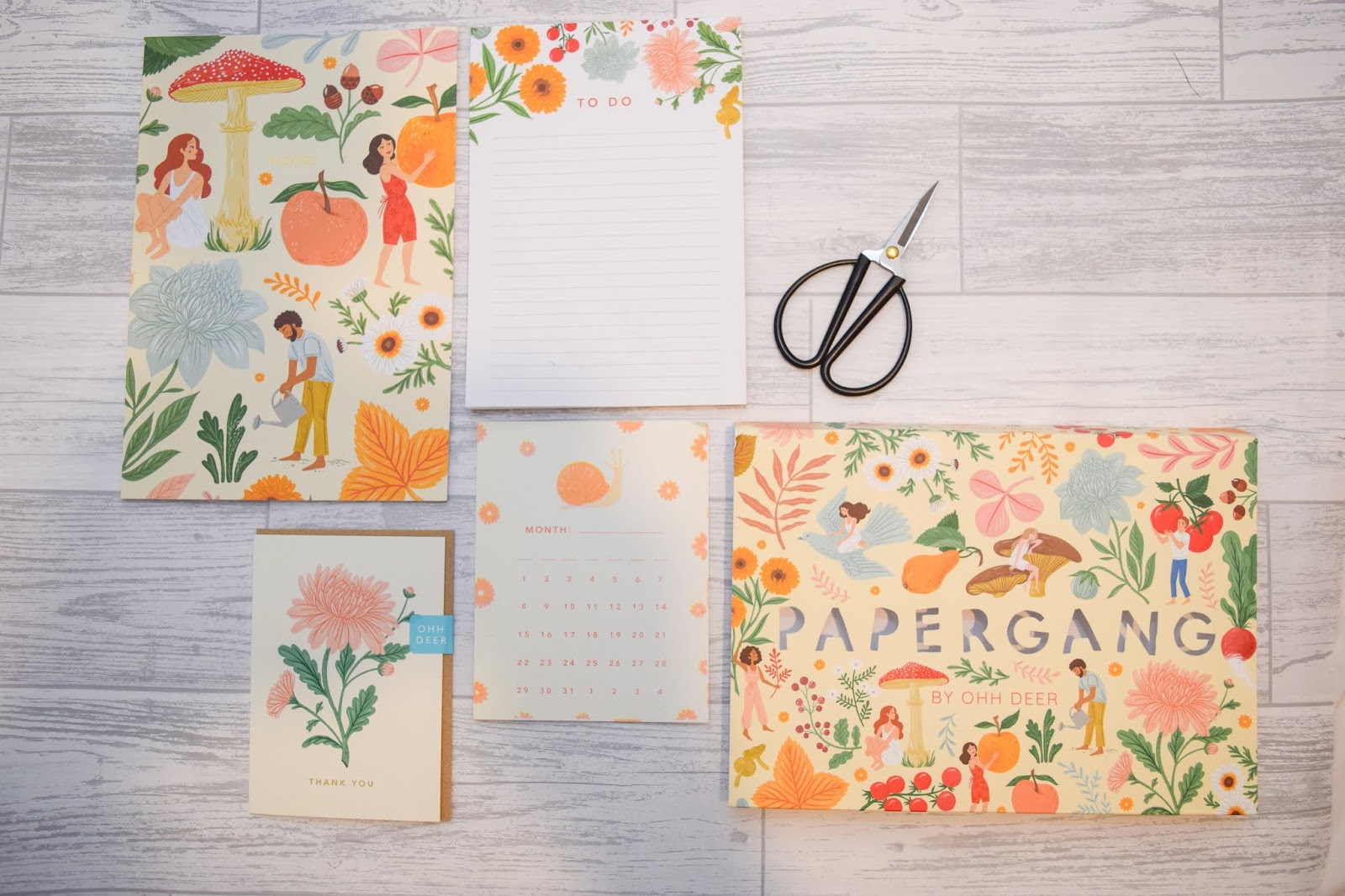 An overview of the contents of a stationery subscription box including a notebook, thank you card, month card, list pad and scissors laying on a white wooden background.