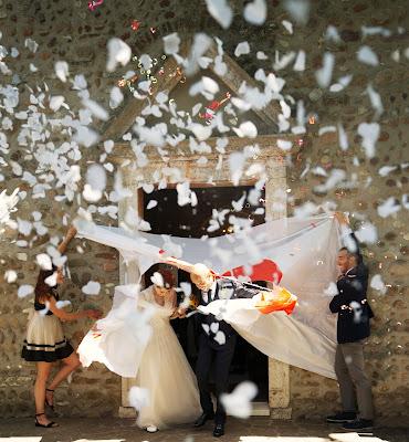 Novios saliendo de la ceremonia mientras atraviesan un lienzo y les lanzan confetti