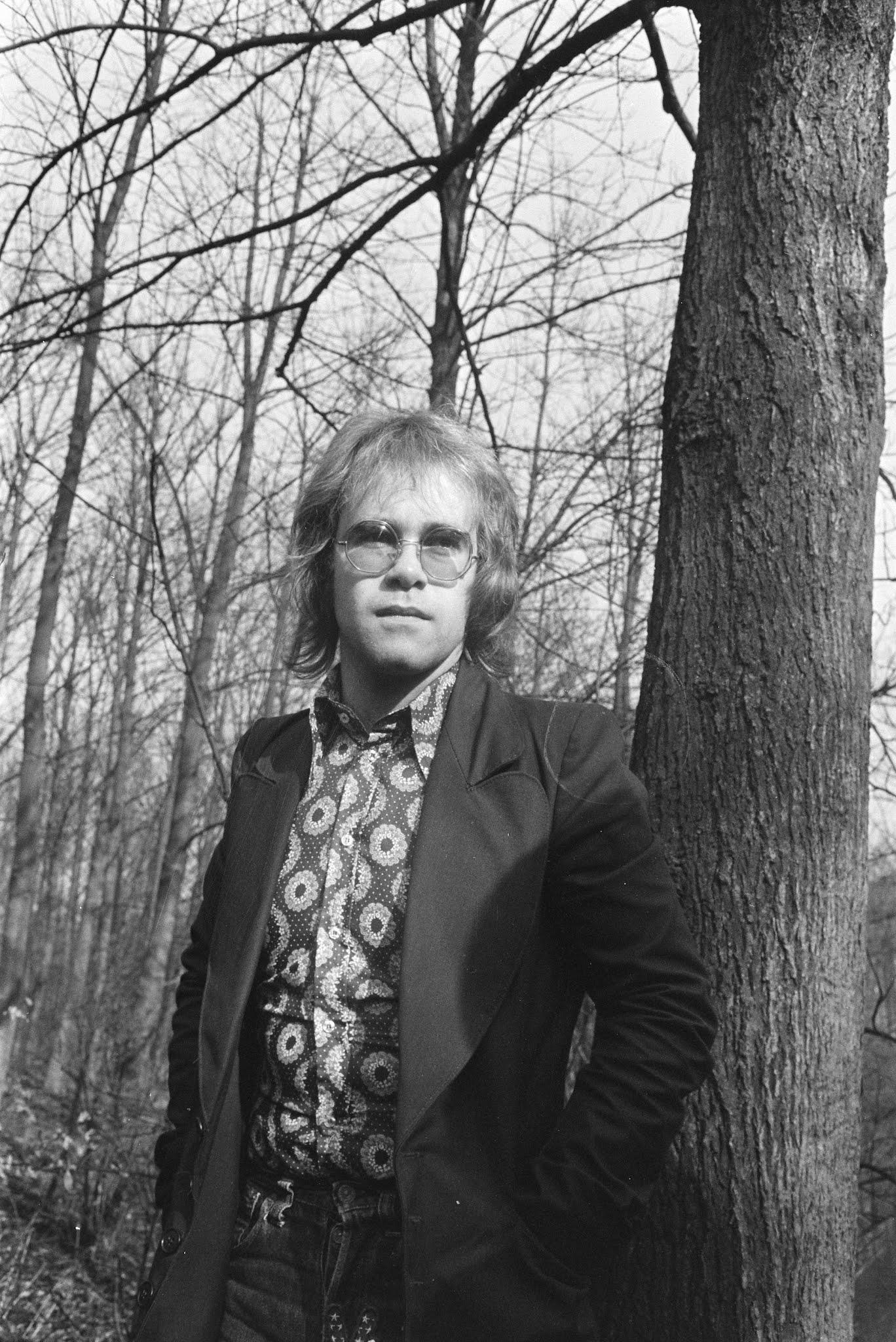 エルトン・ジョンが木のそばに佇んでいる