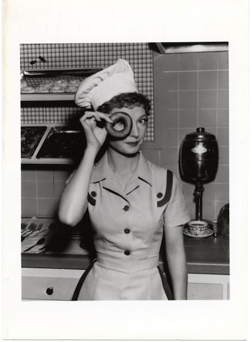 Pert young waitress in restaurant peeking through a donut hole c. 1950s. The The Doughnut Years. marchmatron.com