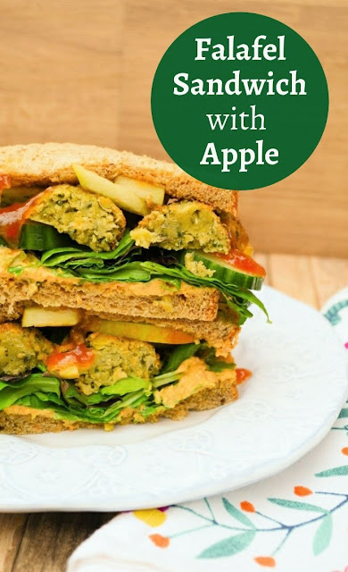 A deep filled falafel and red apple sandwich