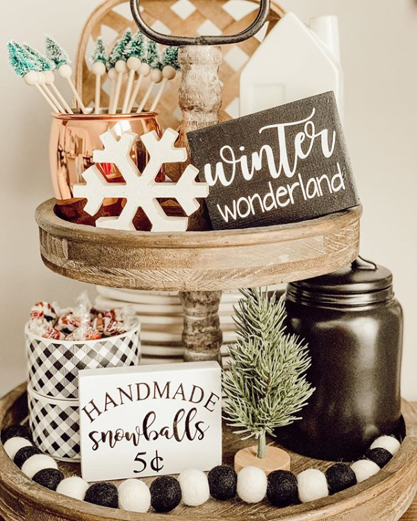 A rustic wooden tiered tray decorated for winter