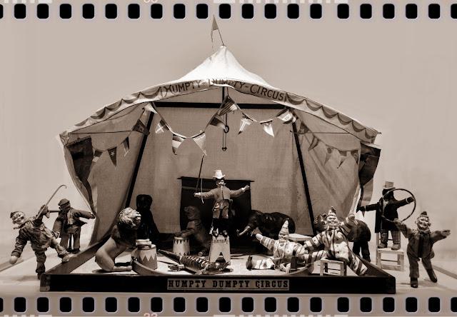 Zirkuszelt mit Holztieren und -clowns