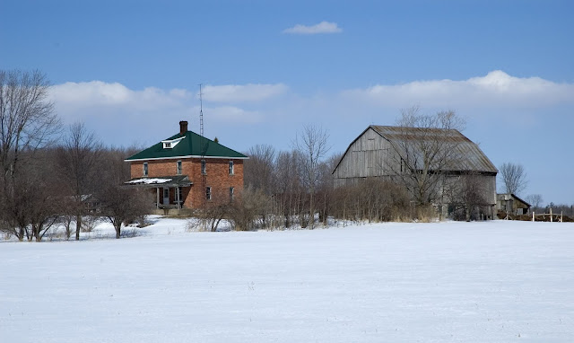 A rural farm in a snow-covered winter field.
