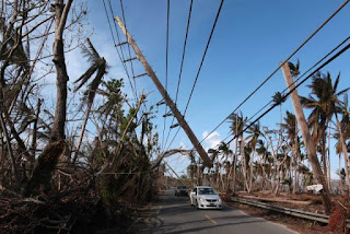Cars drive under a partially collapsed utility pole, after the island was hit by Hurricane Maria in September, in Naguabo, Puerto Rico October 20, 2017. (Credit: Reuters/Alvin Baez)  Click to Enlarge.