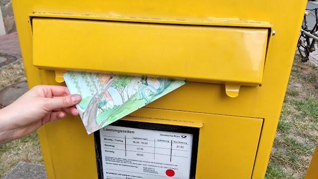Das Foto zeigt die Hand einer Frau, die eine für Kinder illustrierte Postkarte in einen großen gelben Briefkasten der Deutschen Post einwirft.