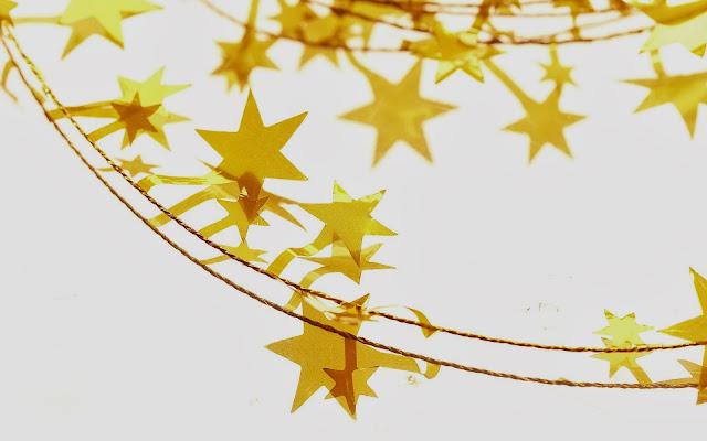 Wallpaper met gele kerststerren aan touw