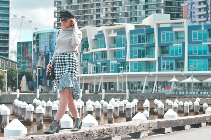 girl fashion blogger in melbourne wharf wearing gingham frill skirt baker boy hat studded boots