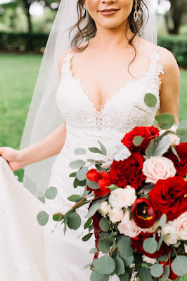 stunning bride in her wedding dress with red and pink bridal bouquet