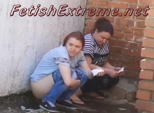 Women pissing at a brick wall (Piss behind brick building)