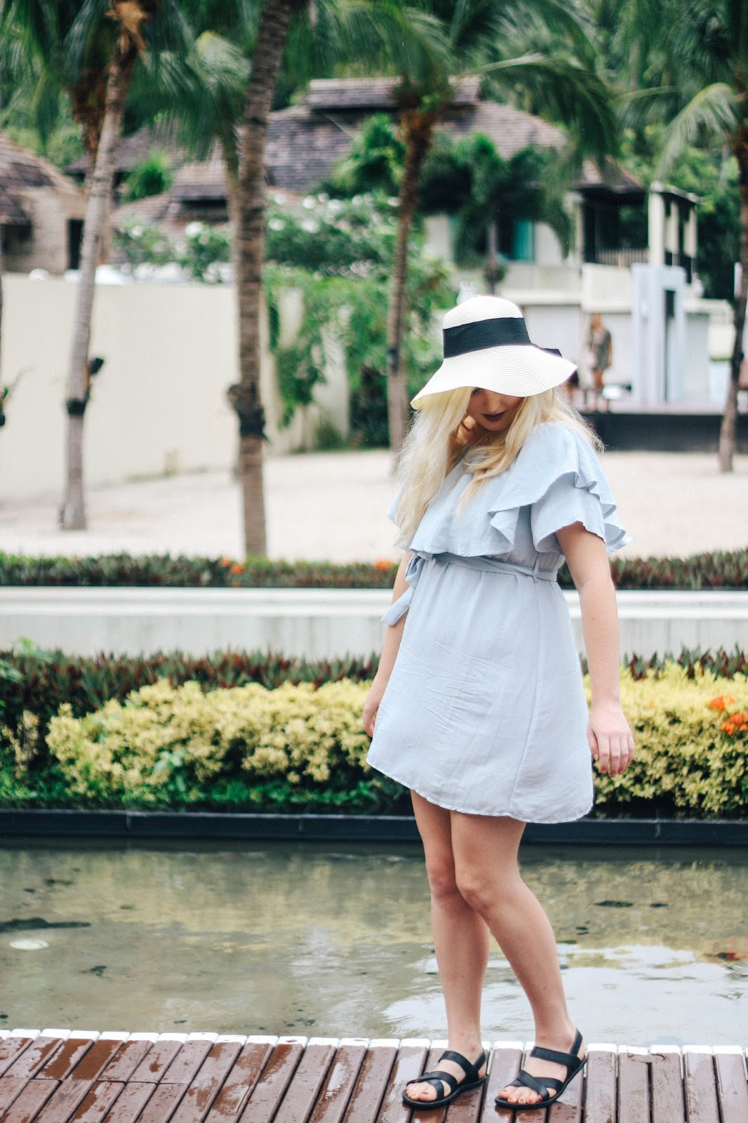 Fashion and Travel Blogger GlobalFashionGal (Brianna Degaston) wearing a TEMT light blue dress and floppy hat at Railay Beach, Thailand.