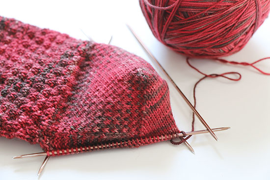 The leg and turned heel on a red hand knit wool sock on metal double point knitting needles next to a ball of yarn on a white background.