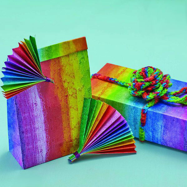 rainbow gift wrap with paper fan ornaments and multicolor yarn bow