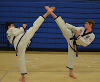 Two teenagers kicking at a martial arts school for teens