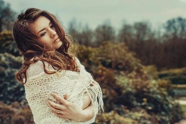 صورة لإمرأة تلف حول جسدها لحاف كأنها حزينة