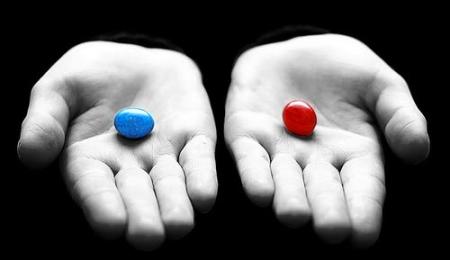 In de ene hand ligt een blauwe pil, in de andere een rode